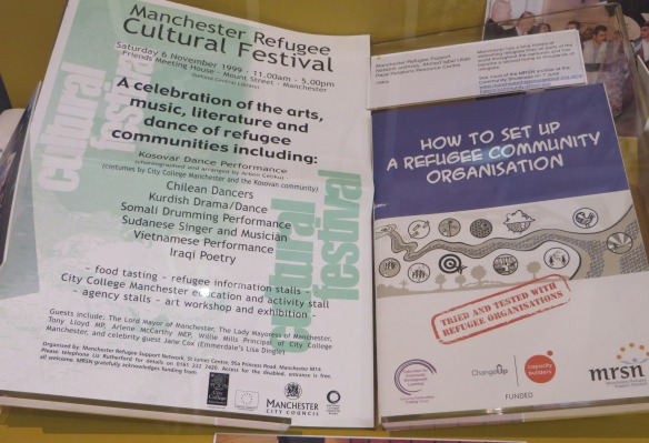 photograph of archive items in a display case, including Manchester Refugee Cultural Festival brochure and te How to set up a Refugee Organisation guidebook